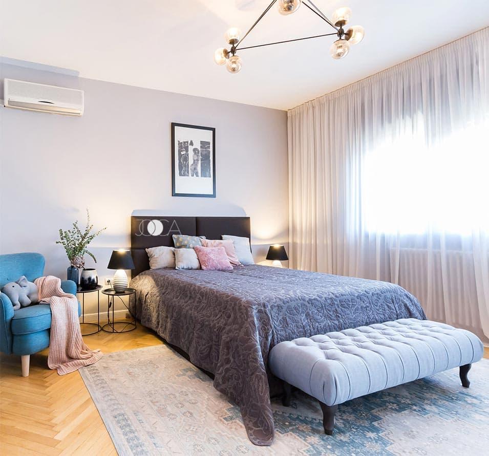 Dormitorul matrimonial nu este foarte incarcat. Patul tapitat este piesa importanta a camerei, iar fotoliul albastru aduce pata de culoare la fel ca in living