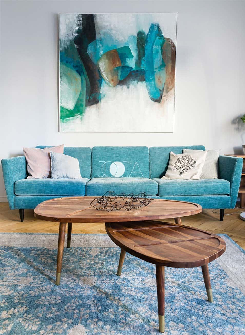 Canapeaua retro, masuta de cafea din lemn, parchetul restuarant se completeaza cu tabloul pictat special pentru acest living luminos
