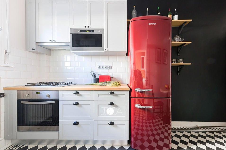 Bucatarie este una mica dar cu personalitate. Frigiderul mare si rosu se potriveste perfect cu mobilierul alb profilat si pardoseala decorativa.