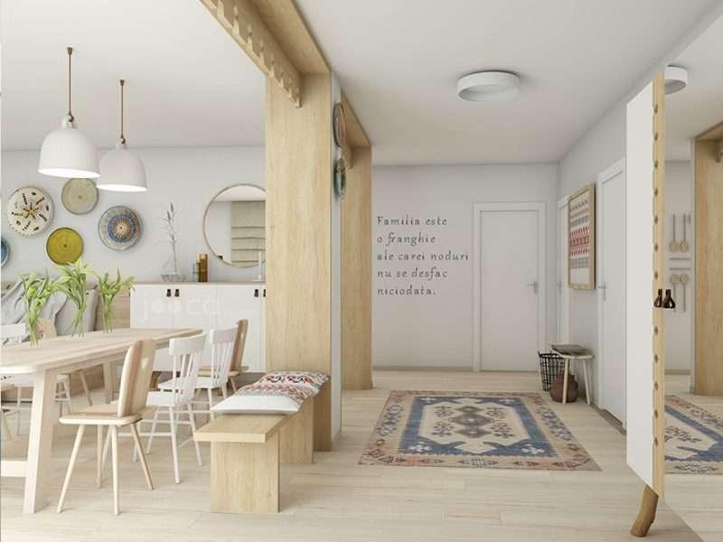 Holul casei este separat de living prin 2 porti metaforice decorate cu panouri traforate, ca cele de la streasinile casei.
