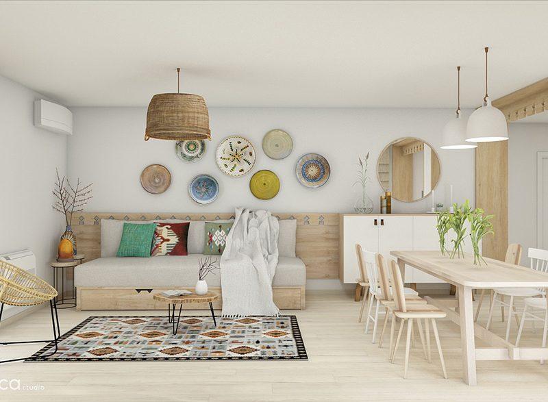 Livingul casei traditionale din container are in prim plan canapeaua de tip lavita si farfuriile de Horezu care decoreaza peretii.