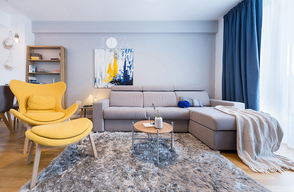In acest living, nuantele de gri ale peretilor, canapelei si covorului compun un fundal neutru pentru accentele de galben si albastru regasite in fotoliu, tablou si draperii.