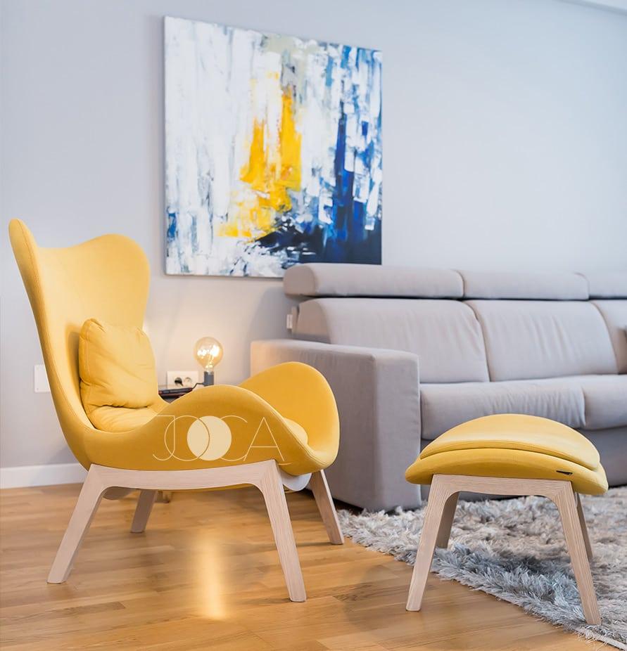 Lazy CFotoliul galben de la Caligaris este piesa centrala a living-ului . Tabloul abstract din spatele canapelei in nuante de albastru si galben solar completeaza amenajarea acestui livinghair Caligaris