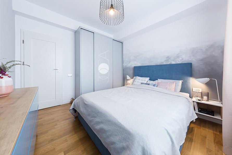 La amenjarea dormitorului am optat pentru un perete pictat manual, cu o textura de norisori, in care am folosit griuri ca si gama cromatica. Patul este tapitat cu o stofa albastra, iar dulapul pentru haine este din mdf vopsit
