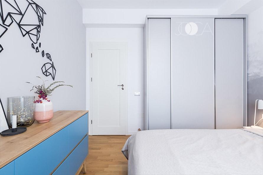 In fata patului se gaseste o comoda de depozitarea, realizata in acelasi stil cu restul mobilierului din amenajare. Cadrul este din mdf furniruit iar fronturile din mdf vopsit in albastru.