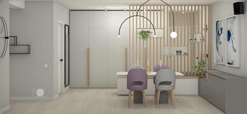 Zona dining-ului este despartita de holul de intrare printr-un panou deschis, realizat din lamele de lemn. Cromatica este baza pe nuante calde de gri, iar petele de culoare sunt scaunele tapitate si cele doua tablouri abstracte.