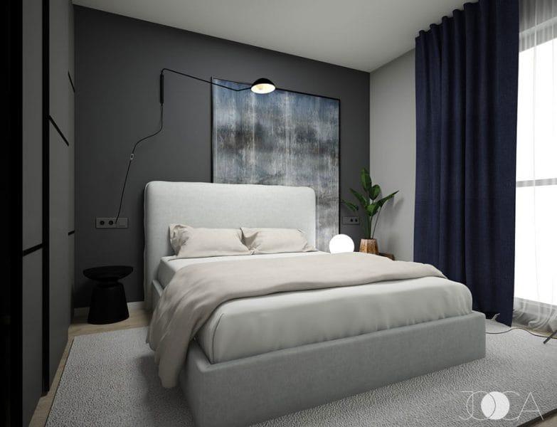 Prin comparatie, poti vedea in amenajarea acestui dormitor ce impact poate avea un perete gri inchis. Dramatismul este accentual prin contrastul cu tapiteria gri deschis a patului, iar sursele de lumina zonale contribuie la scenografie. Draperiile bleumarin si textura tabloului cu nuante de albastru completeaza spatiul.