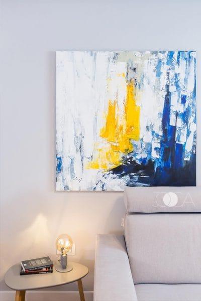 tabloul din spatele canapelei este pictat manual intr-un stil abstract, folosind tonuri de galben si albastru.