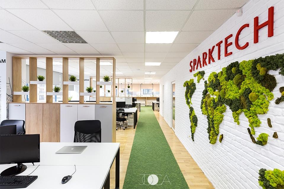 Zona open-space este simpla si luminoasa. Birourile sunt despatite printr-un ansamblu de mobilier cu deschis, iar harta lumii din licheni verzi este amplasata pe un perete din caramida aparenta alba.