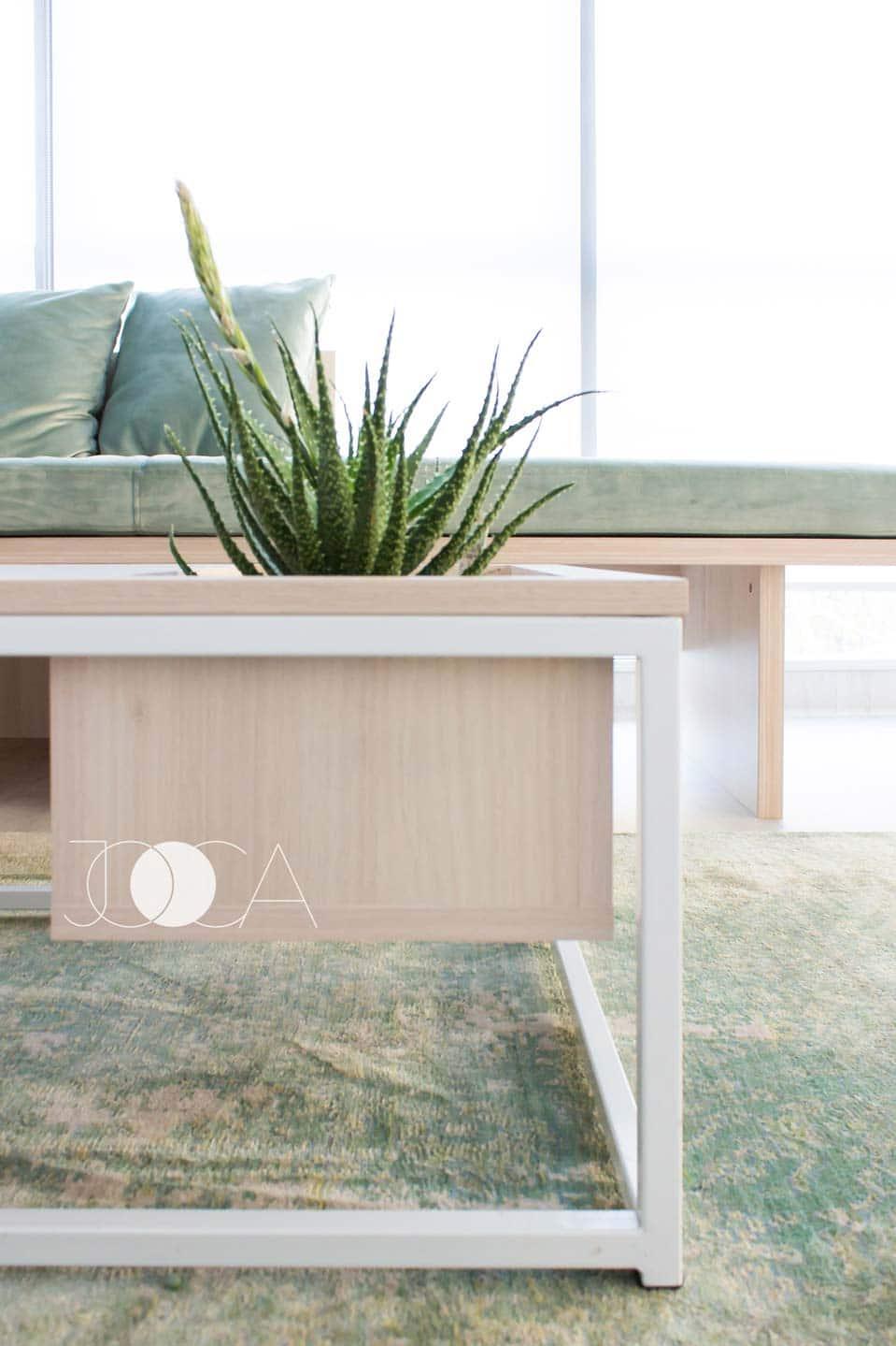 Zona de lounge din biropul CEO-ului este formata dintr-o bancgeta dip pat de zi si o masuta cu dadru metalic. Covorul verde completeaza atmosfera cosy.
