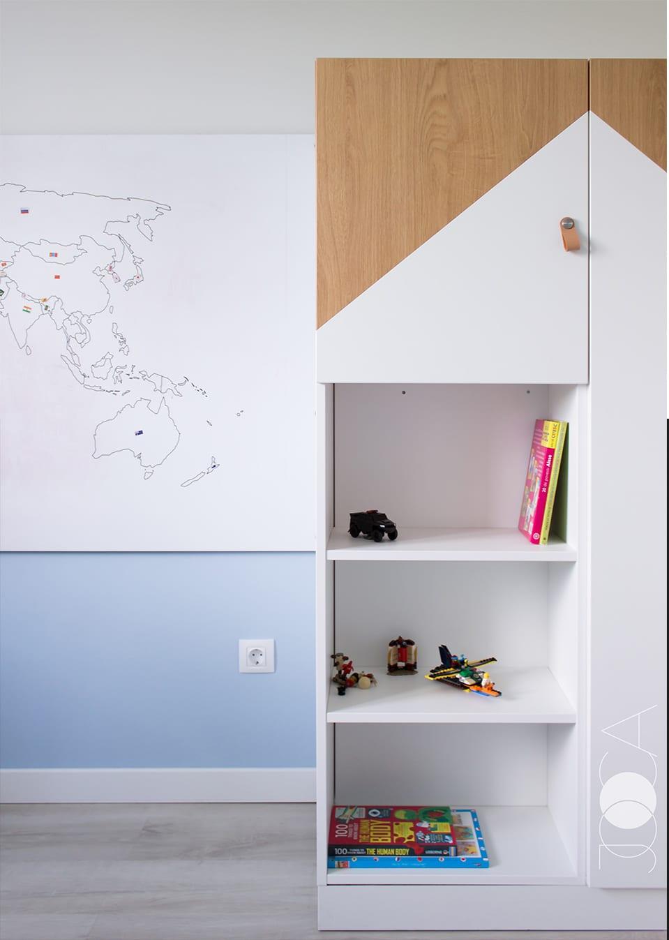 Corpul de depozitare din camera baiatului este realizat pe comanda, sub forma unei casute. Langa, se afla harta lumii, printata pe un panou de tipul whiteboard.