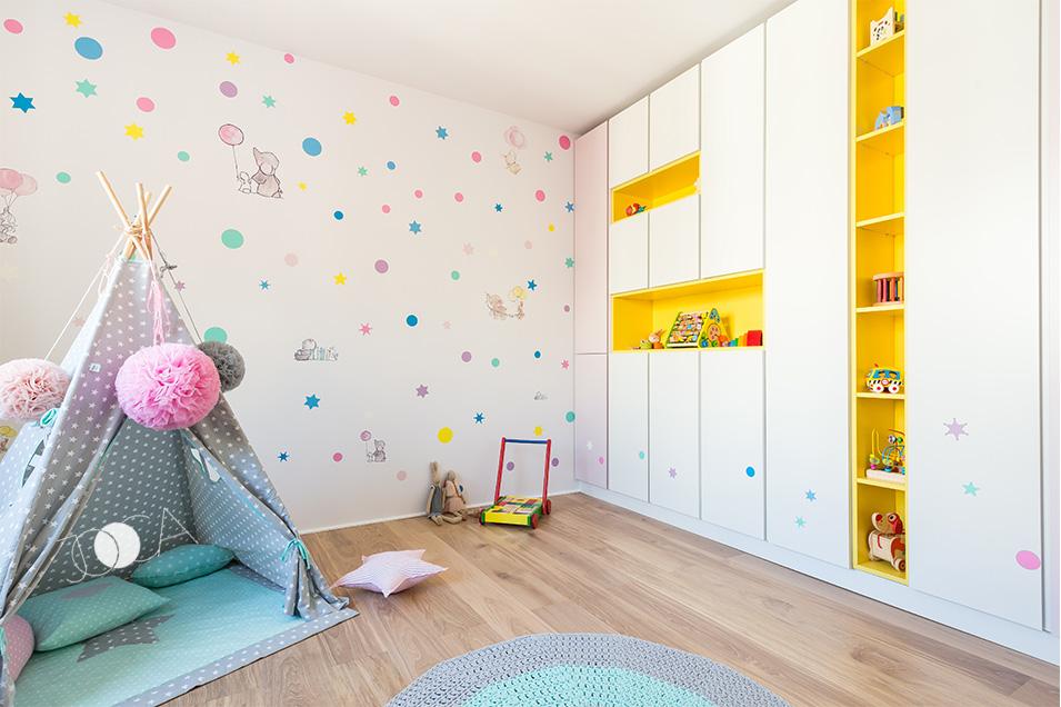 Camera fetitei este o explozie de veselie si culoare. Rafturile deschise din mdf galben sparg liniaritatea simpla a dulapului. Peretele este decorat cu stickere multicolore.