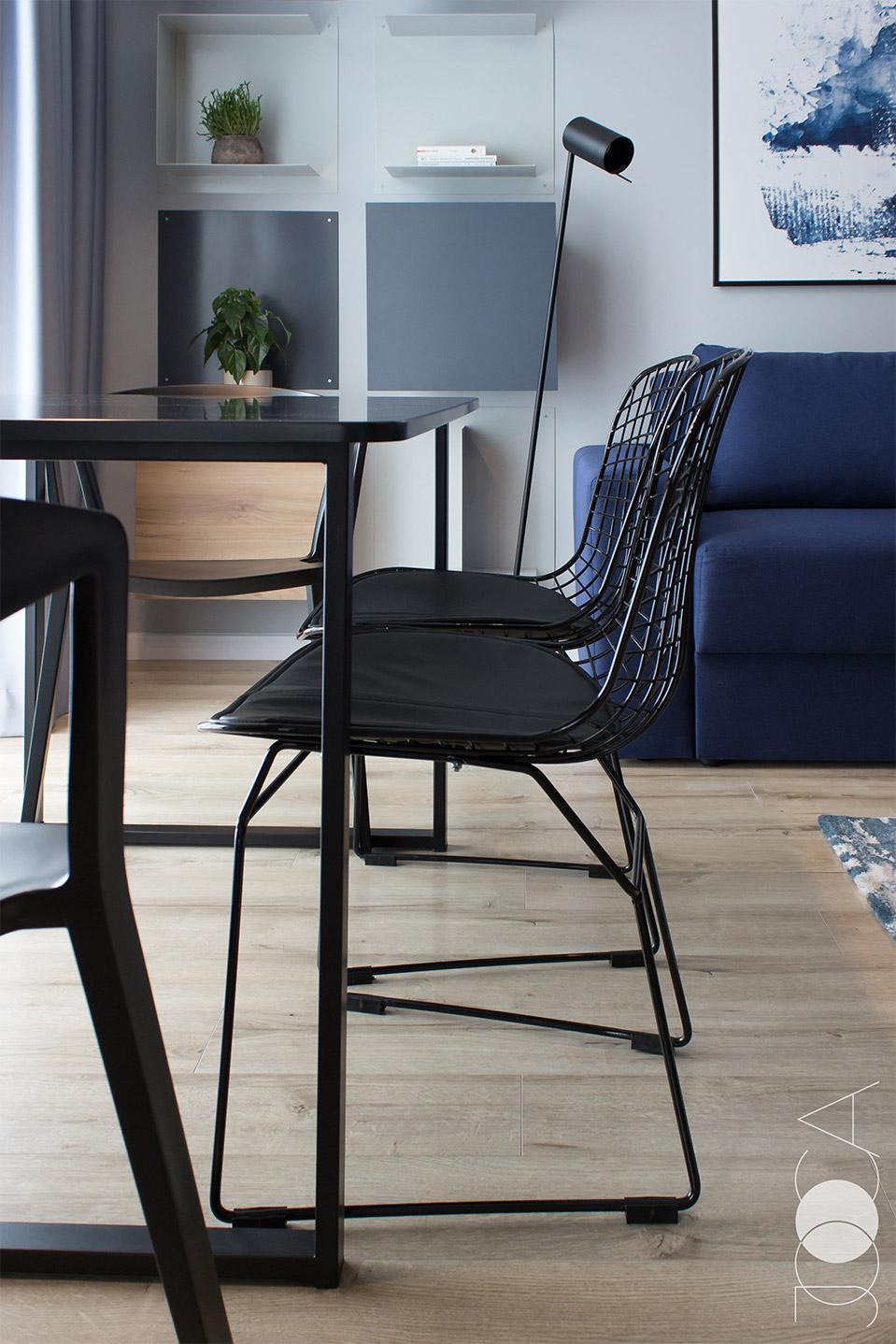 Negrul predomina in aceasta amenajare. Metalul se regaseste la scaune si la cadrele mesei.