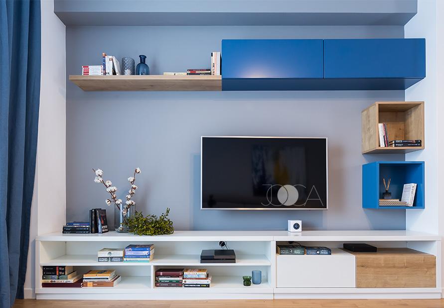 Biblioteca din zona TV-ului este un joc de volume inchise sau deschise, cu accente de lemn si de albastru.