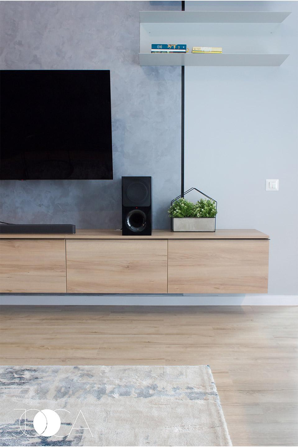 Comoda este din pal si este suspendata in perete. Peretele cu tv-ul este inpartit in 2 prin folosirea a 2 tipuri de vopsea.