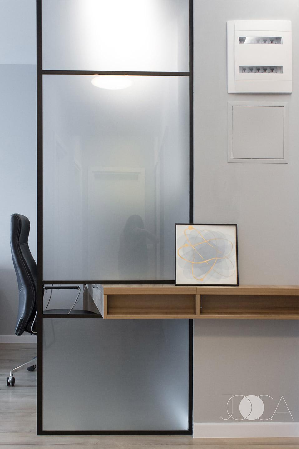 Zona de birou este separata de hol printr-un panou de sticla, cu cadru metalic. Blatul biroului se continua pe hol prin acest panou.