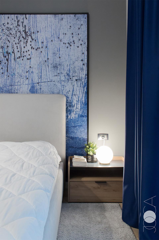 Draperiile albastre si tabloul din spatele tabliei sunt cele care dau culoare dormitorului.