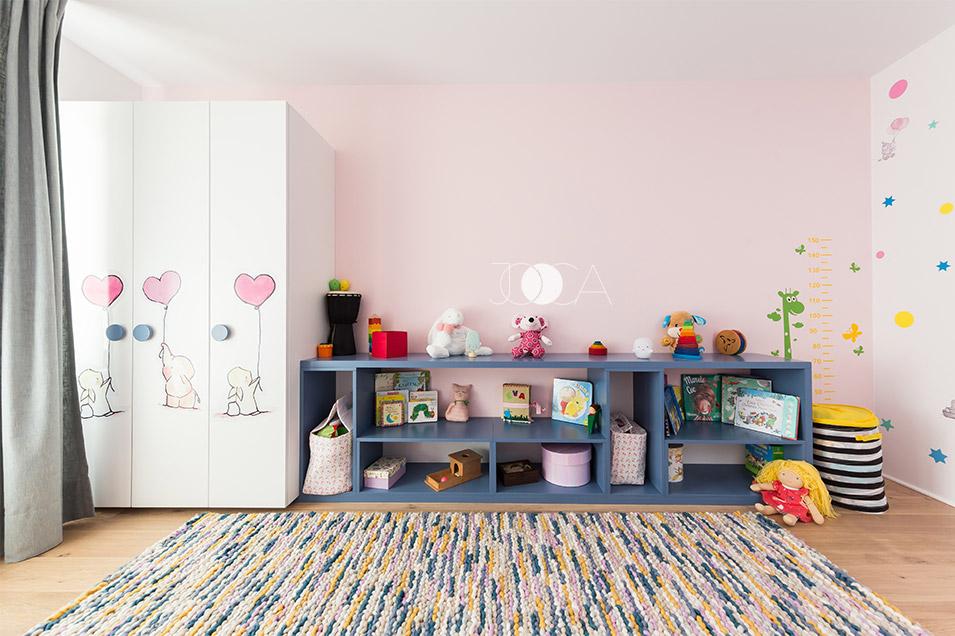 Mobilerul este gandit dupa principiul Montessori. Comoda deschisa ii ofera acces usor fetitei in zona rafturilor.