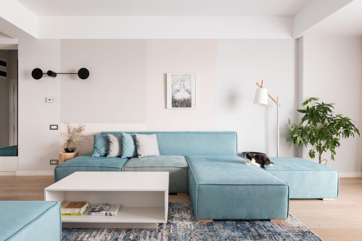 Livingul generos al apartamentului a permis zooficarea in spatiu de zi si loc de luat masa. Canapeaua modulara in culoarea bleu este piesa centrala a casei. Aplica neagra de pe perete adauga o lumina ambientala placuta.