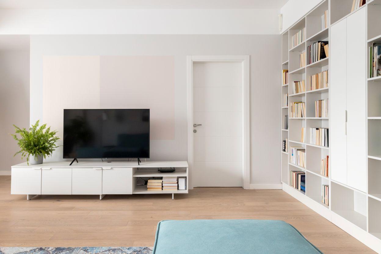 Comoda tv este simpla, in aceeasi culoare ca si biblioteca, un gri foarte deschis. Peretele din spatele tvului este vopsit in mai multe nuante pastelate, ce creeaza un joc geometric fin.