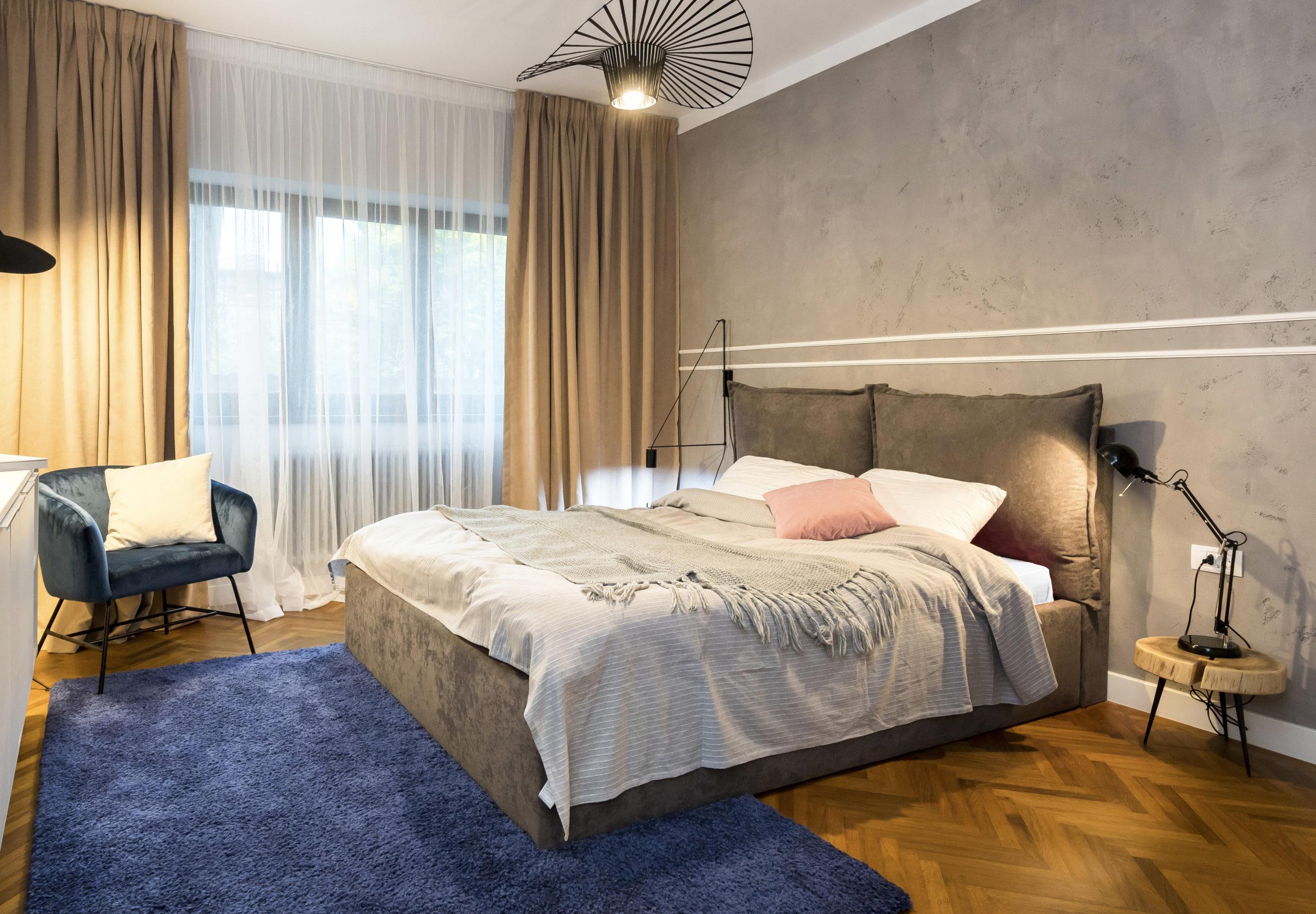 Peretele din spatele patului este vopsit cu o decorativa cu aspect de beton. Textura de beton este elementul care contrasteaza cu stilul retro al amenajarii.