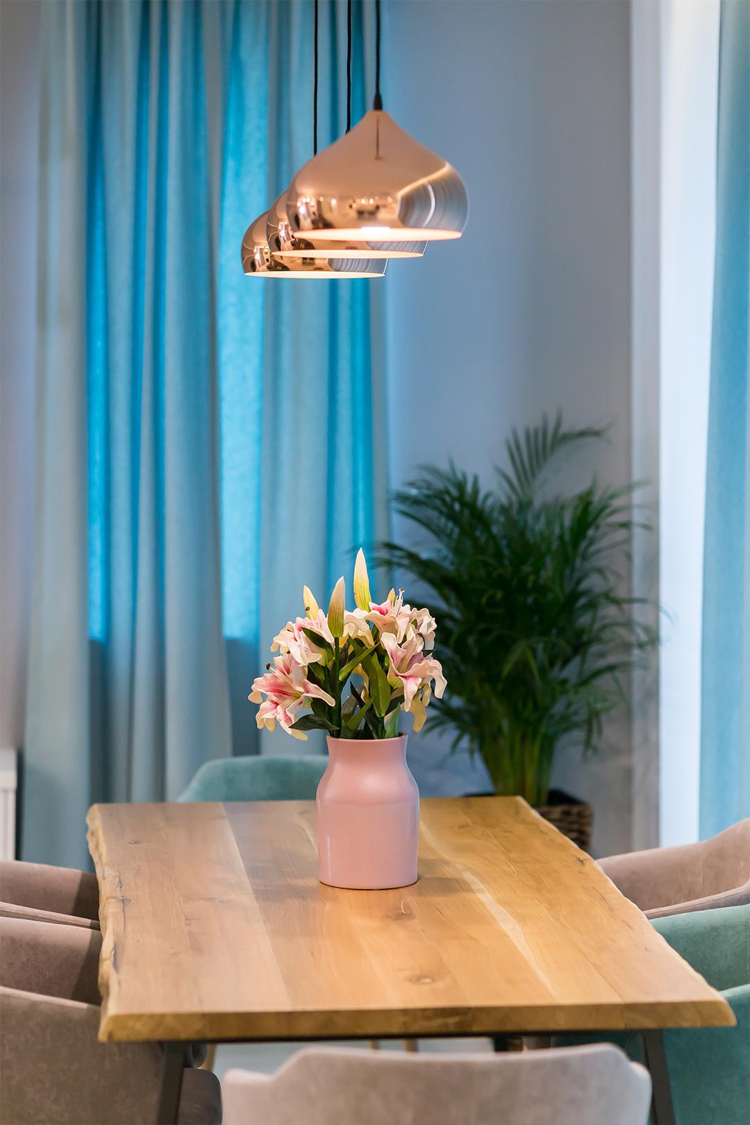 Corpurile suspendate in nuanta cuprului reprezinta un accent glam, care contrasteaza cu aspectul brut al mesei.
