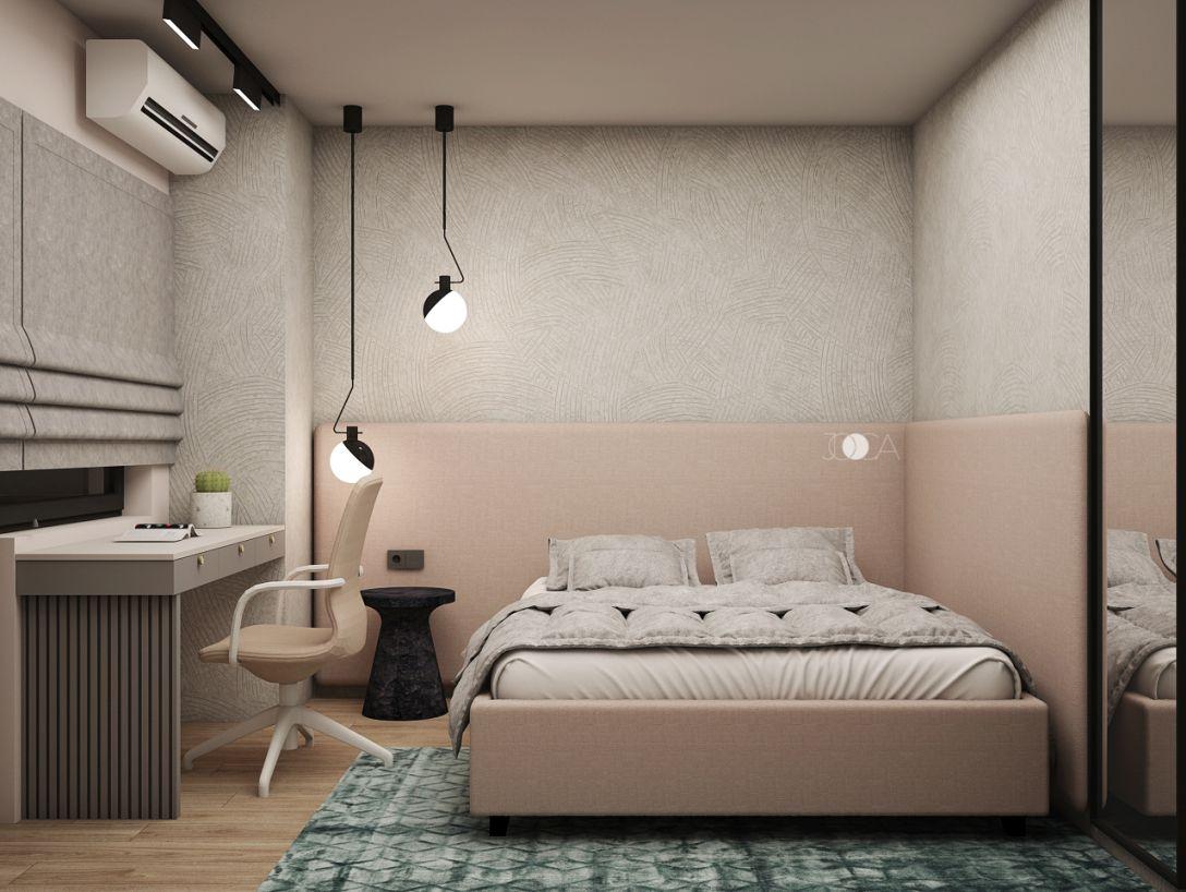 Patul din dormitorul fetiteti are o tablie pe doua laturi, tapitata intr-o stofa de culoare roz, iar vopseaua decorativa de pe perete creeaza un fundal neutru.
