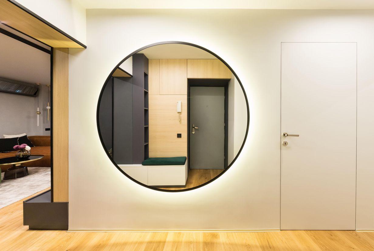 Antreul apartamentului. Pe peretele din fata iti atrage atentia oglinda rotunda, centrata pe centrul peretelui