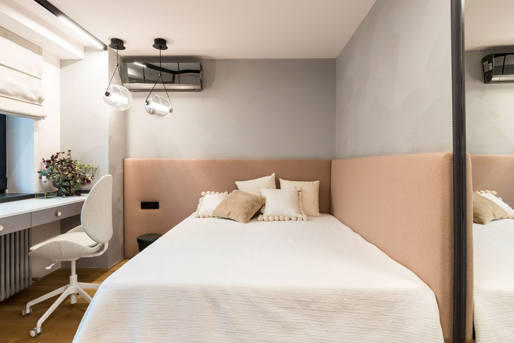 Dormitorul fetitei este simplu și discret, cu patul înconjurat pe două lături de o tăblie tapițată și o textura jucăușă de vopsea decorativă pe perete