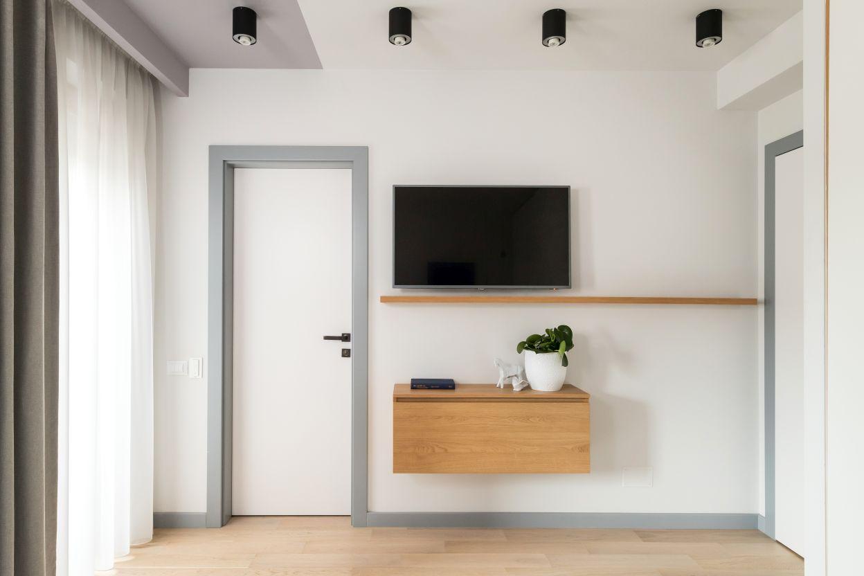 Peretele cu tv-ul si usa de intrare in baie este simplu decorat, cu cateva elemente din lmen. Un alt element important in designul acestei case este plinta gri, in aceeasi culoare cu pervazul usilor.