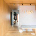 Holul de la intrare este placat pe perete si plafon cu acelasi lemn de la parchet. Astfel, impreuna cu lamelele de lemn de la marginea scarilor, formeaza un volum de lemn, o casa in caa.