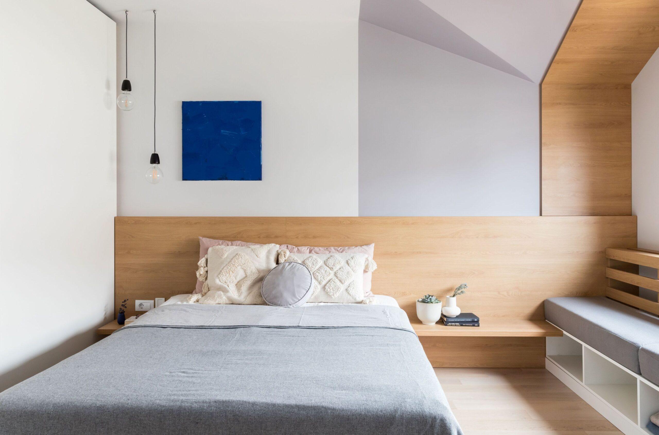 Zona de la fereastra din dormitorul matrimonial este placata cu lemn. Forma neregulata a plafonului ne-a insiprat in createa unor volume de lemn si de vopsea gri.Tablia patului este simpla, de lemn.