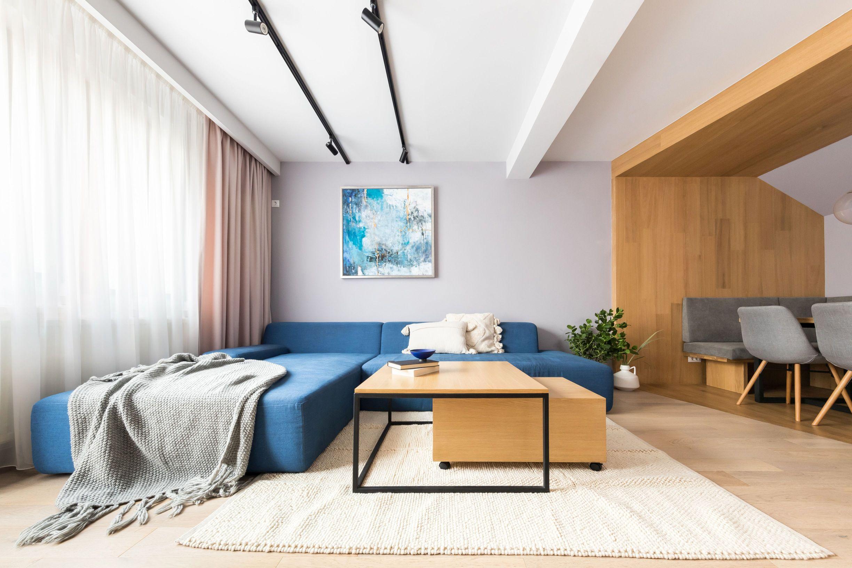Diningul este separat vizual de living printr-un volum placat cu lemn masiv se stejar. Canapeaua albastra este centrul atentiei in acest spatiu.