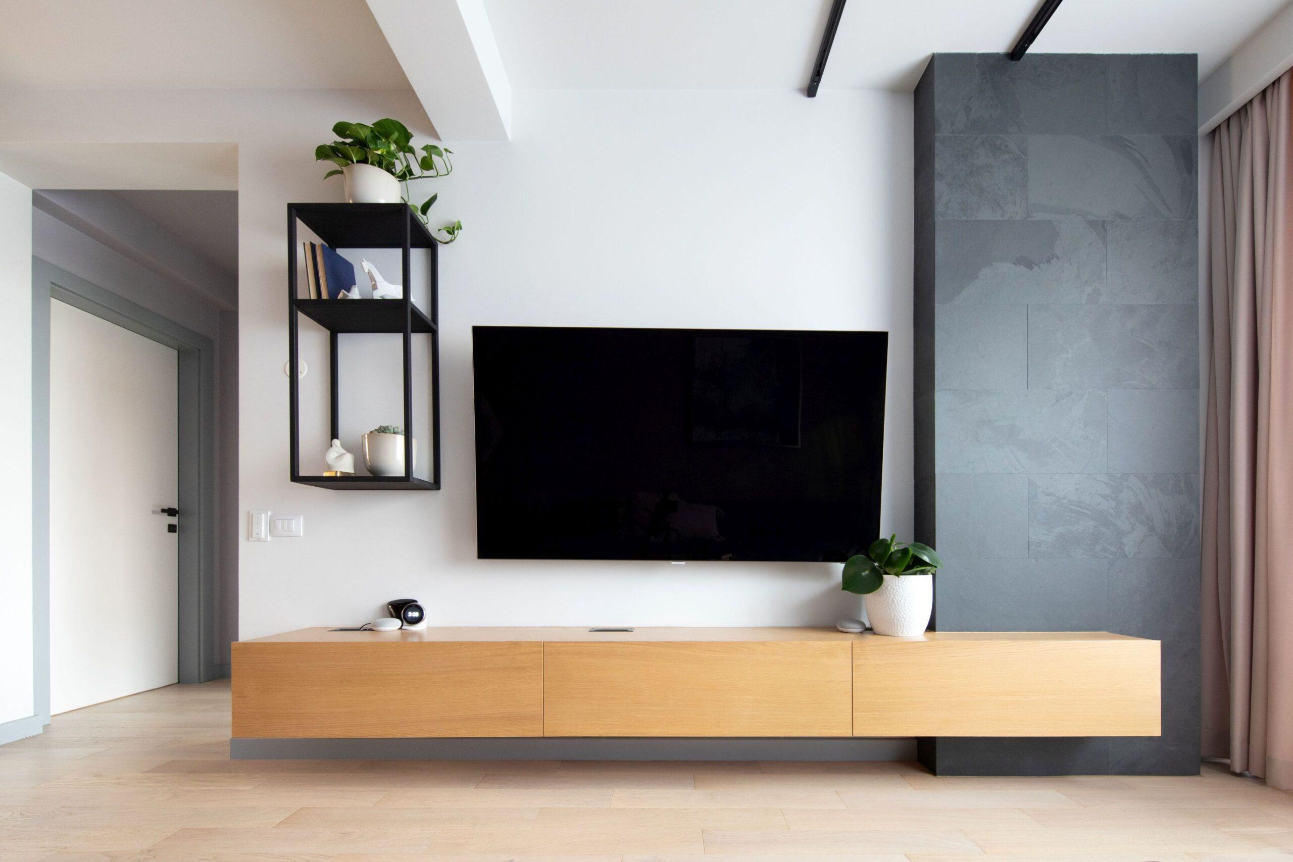 In zona e tv comoda de lemn se intersecteaza cu un volum vertical placat cu ardezie neagra. Compozitita este completata de un mic raft suspendat metalic.