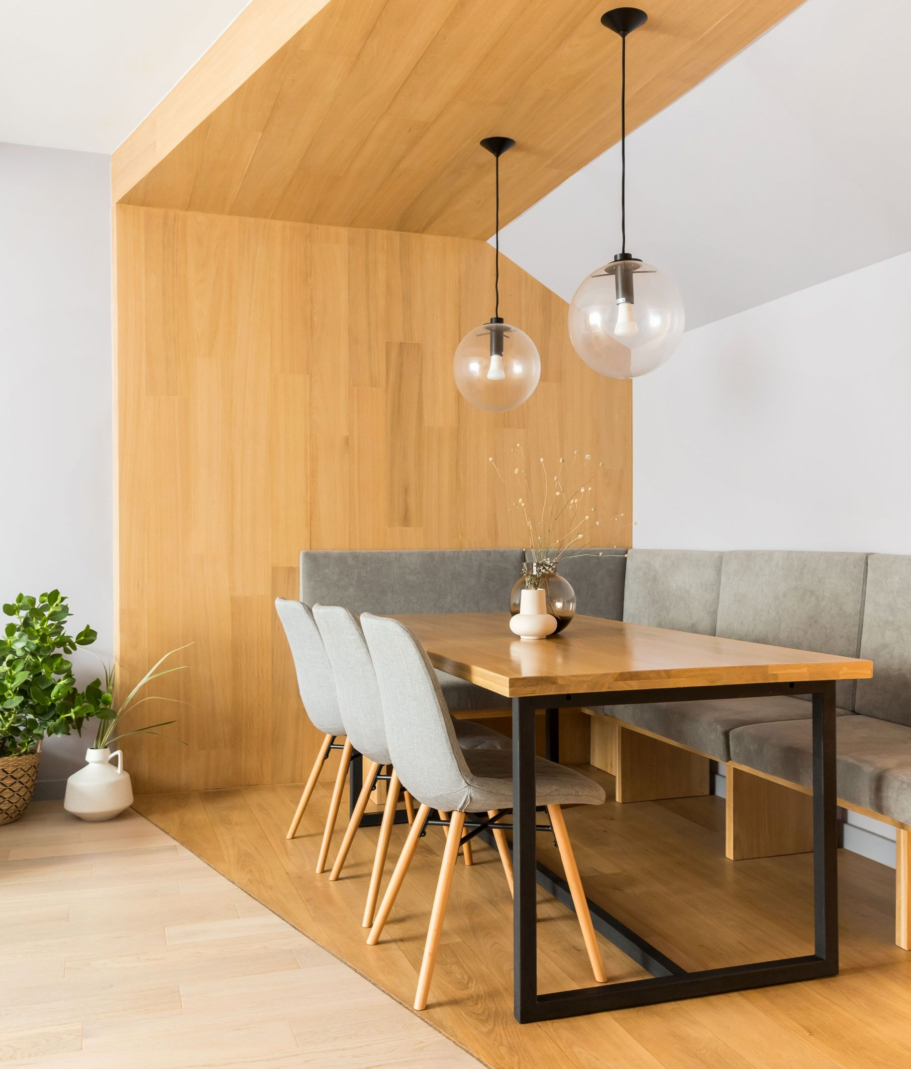 Volumul de lemn ce imbraca locul de luat masa creeaza o zona calda si confortabila. Scaunele de dining si bancheta gri neutre pun in valoare volumul de lemn prin simplitatea lor.