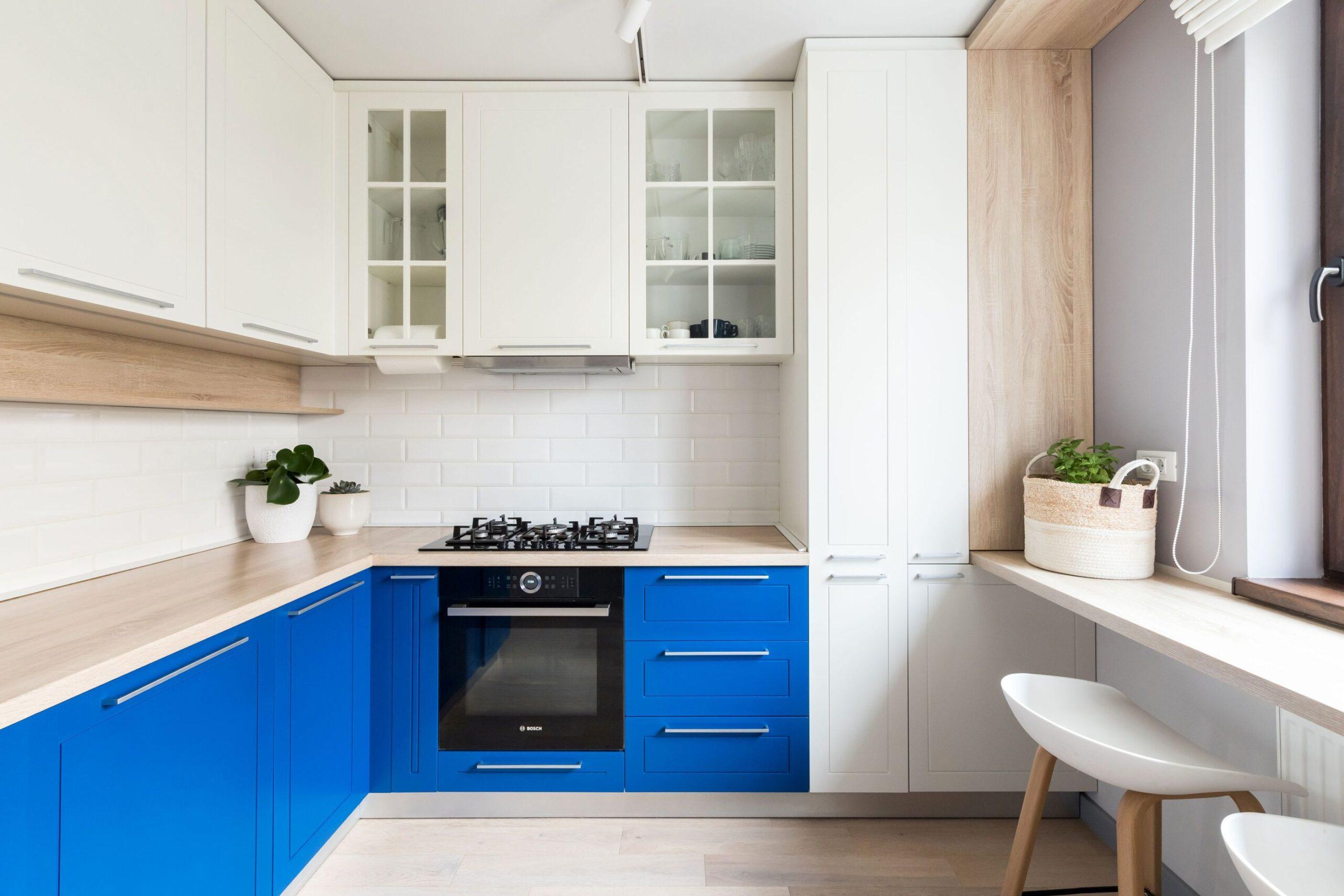 In bucatarie regasim acelasi albastru de berlin la corpurile de mobilier de jos, Corpurile suspendate sunt albe, iar blatul este de lemn.